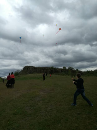 Children flying kites on a darkening landscape